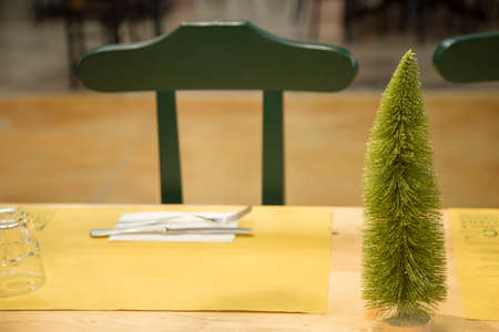horizontal image with detail of a green chair at the restaurant with a small christmas tree on the table