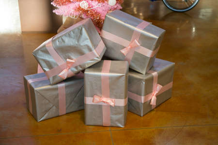 horizontal image with detail of five christmas presents decorated with pink ribbon under a pink christmas tree