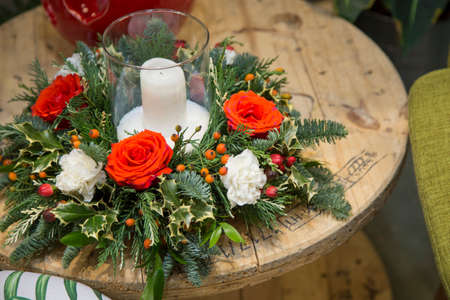 horizontal image with detail of a Christmas flower arrangement with red and white roses and a candle over a wooden table