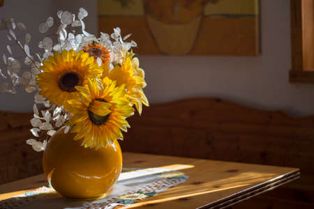 horizontal image with detail of a yellow vase with sunflowers flowers over a table with light coming in through a window