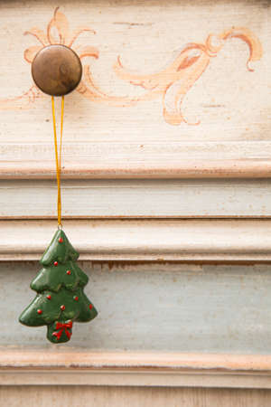 horizontal image with detail of a cute Christmas tree-shaped Christmas decoration hanging from a drawer knob Banco de Imagens