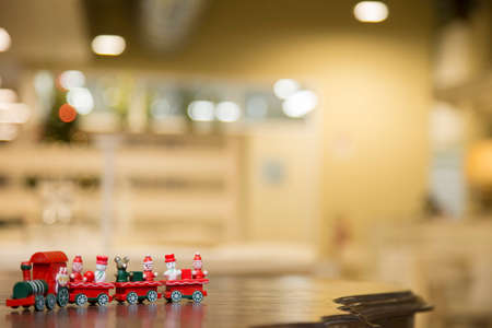 horizontal image with detail of a small Christmas toy train over a shelf with blurred background Banco de Imagens