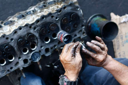 dirty, greasy Asian mans hands, oiling and greasing valves and pistons and inserting into an engine block in a dirty workshop in Thailand, Southeast Asia