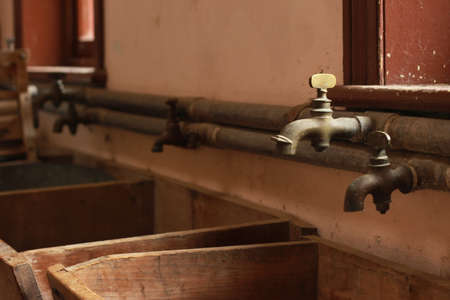 vintage antique laundry plumbing taps and wooden sinks in an old home, now museam, in Victoria, Australia Archivio Fotografico