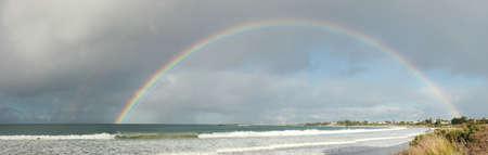Gran arco iris de medio círculo completo que se extiende a través del cielo hacia el océano en Apollo Bay, Victoria, Australia