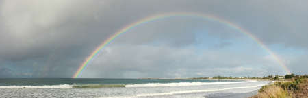 large complete full half circle rainbow stretching across the sky into the ocean at Apollo Bay, Victoria, Australia