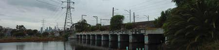 graffiti covered metropolitan railway bridge crossing a small river on it's way to the city CBD, outer Melbourne suburbs, Victoria Australia