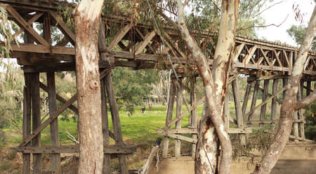 old timber hardwood discontinued railway bridge river crossing in a rural farming town, Victoria, Australia