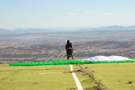 lone amatuer Australian man preparing his equipment for a running jump paraglide from a popular paragliding location in Manilla, rural New South Wales, Australia 14th May 2019