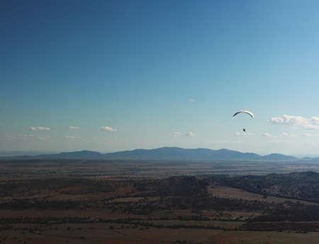 lone paragliding man drifting through the air chasing hot swells at an internationally popular paragliding location, Manilla, rural New South Wales, Australia. 14th May 2019