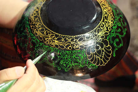 hands of a craftswoman painting decorative lacquer on traditional plates and bowls at a craft night market stall in Northern Thailand, Southeast Asia