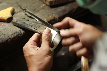 hands and tools of a professional silversmith working on a piece in his traditional workshop, Northern Thailand Stock fotó