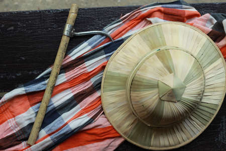 flat lay details showing the tools and colorful clothing and bamboo woven hat of a traditional Northern Thailand Thai Elephant Mahoot trainer, Southeast Asia