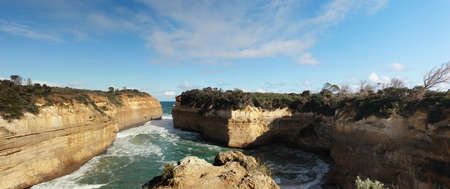 panoramic view of wild winter waves crashing into Loch Ard gorge, famous site of a shipwreck, great ocean road, Southern Victoria, Australia.