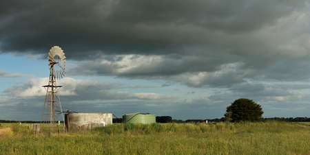 panoramic of a water wind mill next to a large water storage tank on an agricultural sheep stock farm in rural Victoria with dark rain clouds in the sky