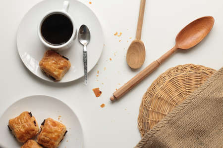 Flat lay of fresh and relaxed settting of black coffee and Pan Au Chocolate French inspired afternoon tea arrangement with clean white bakcground with copy space and timber and brown accents and textures