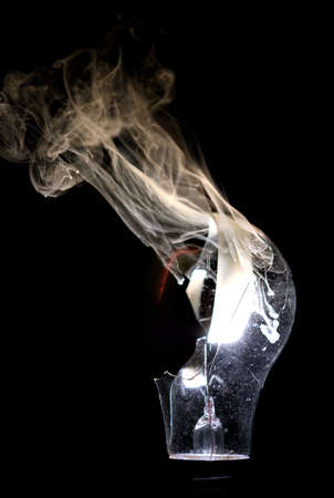 electric bulb: A broken bulb in the process of burning out with smoke curling above.