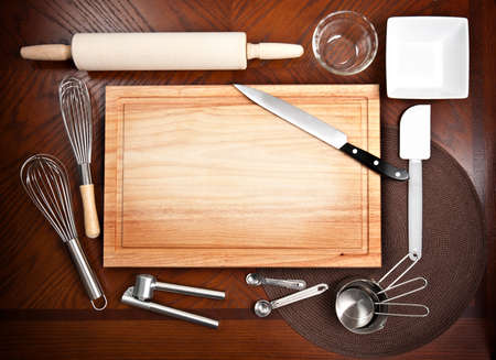 Various cooking tools and utensils arranged around a cutting board