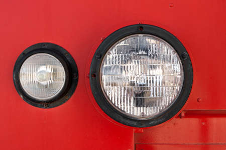headlights: A close up view of the round headlight on an antique fire engine.