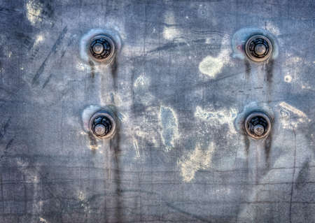 corroded: Four bolts on a corroded metal background.  Great as a background or for texture use.