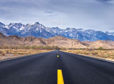 lone pine: Y carretera vac�a se dirigi� a Lone Pine, California Mount Whitney y los cerros orientales de Sierra se pueden ver en el fondo Foto de archivo