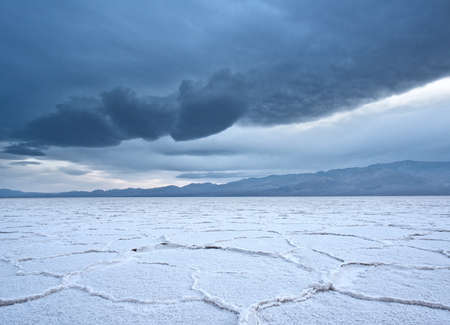 desert storm: Salt polygons on the Badwater Salt Flats in Death Valley National Park as an ominous storm rolls in