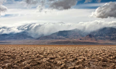 The salt formations at Devils Golf Course in Death Valley National Park   A storm rolls in over the mountains in the distance  Stock Photo - 12885466