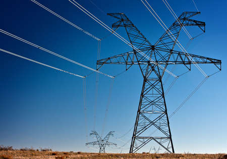Several large high voltage power transmission towers silhouetted Stock Photo - 16799752