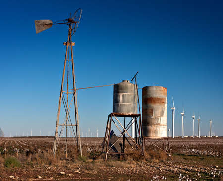 rusted old broken windmill with tanks in a cotton field with wind turbines in the background photo