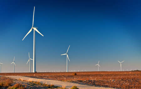 Several large wind turbines in a wind farm located in West Texas   A dirt Road is in the foreground Stock Photo