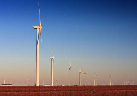 Wind Turbine farm located in a cotton field in West Texas   The cotton has been harvested as is bailed for pick up  photo