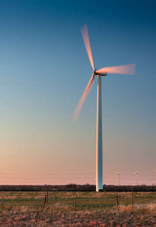 Tall wind turbine in a field in West Texas   Blades are showing motion blur photo