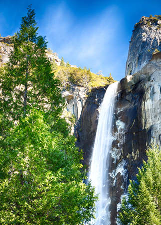 yosemite national park: Bridalveil Falls during a clear winter day   Ice is forming on the rock wall behind the falls