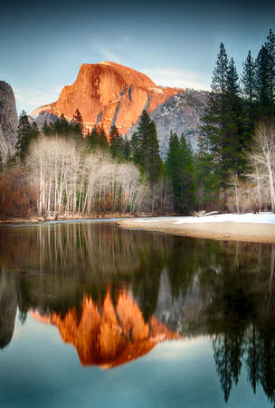 half and half: View of half dome at sunset reflected in the Merced River Stock Photo