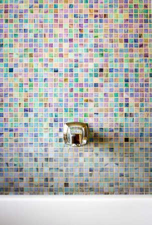 Modern faucet against a mosaic glass tile wall