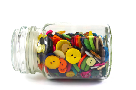 lieing: Colourful haberdashery buttons in a glass jar lieing horizontally on a white background.