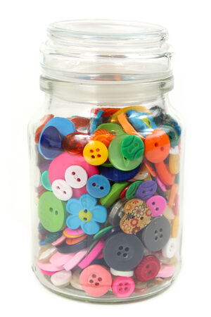 haberdashery: Colorful Haberdashery buttons in a glass jar. Vertical on White background.