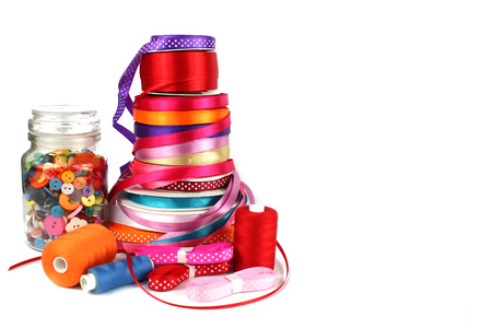 Colorful ribbons, sewing, craft and haberdashery items on a white background with copy space