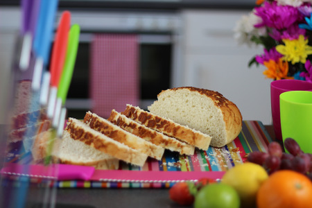 preperation: Colorful kitchen scene with sliced fresh bread on a cutting board.
