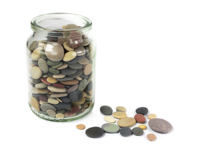 Pebbles or Beach stones in a glass jar on white background