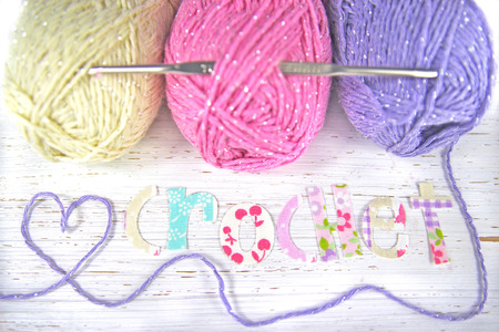 crochet: Crochet background, 3 balls of pastel colored woolyarn. Yarn makes a heart shape next to the word crochet made from cut out fabric letters.