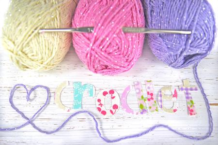 Sfondo Crochet, 3 palline di pastelli colorati di lana / filato. Filati fa una forma di cuore vicino alla parola 'uncinetto' fatto da lettere ritagliate in tessuto. Archivio Fotografico - 31883128