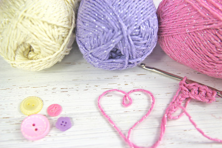 Crochet scene. Yarn Wool pastel colours with crochet hook heart and buttons Stockfoto