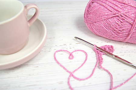 pink crochet background with yarn heart and coffee cup and crochet hook on wooden backround Stock Photo
