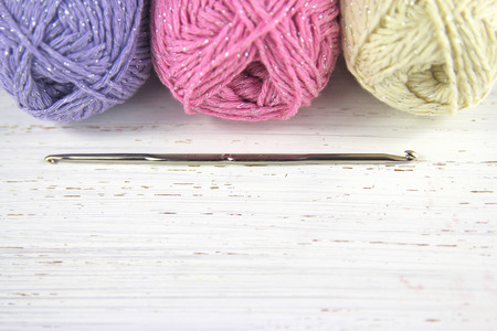 Yarn Wool pastel colours with crochet hook and copy space on distressed wood background Standard-Bild