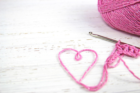 pink crochet background with yarn heart on white rustic wooden background with copy space