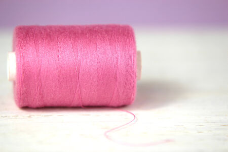haberdashery: Haberdashery pink thread on white rustic wooden and lilac background