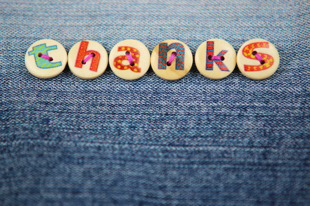 craft background: the word thanks spelled out in lettered buttons on a denim craft background.