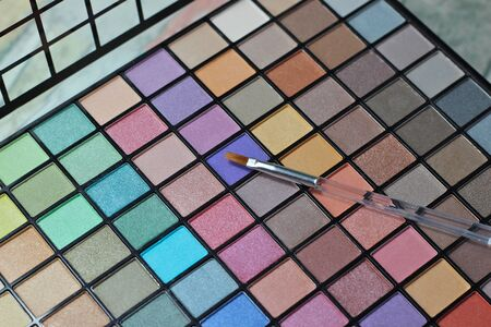 Eyeshadow makeup large palette with applicator brush.