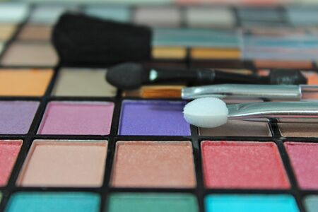 make up brushes: eyeshadow palette with make up brushes. Focus on applicator Stock Photo